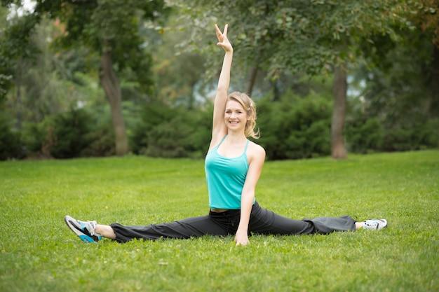Schöne junge frau, die übungen im park ausdehnend tut.