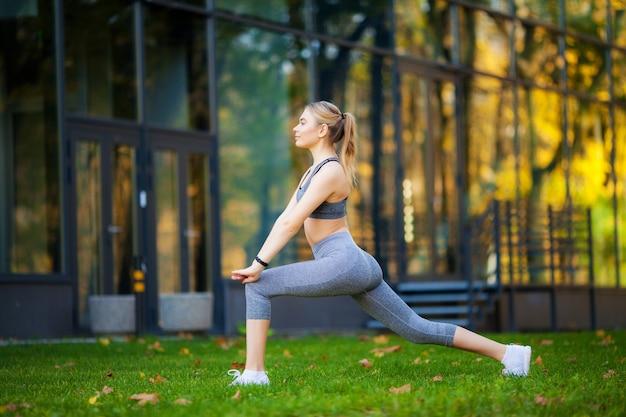 Schöne junge frau, die übungen im park tut