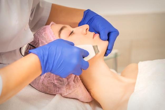 Schöne junge frau, die ultraschallkavitationsgesichtsreinigung im schönheits-spa-salon erhält