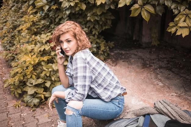 Schöne junge frau, die um telefon ersucht