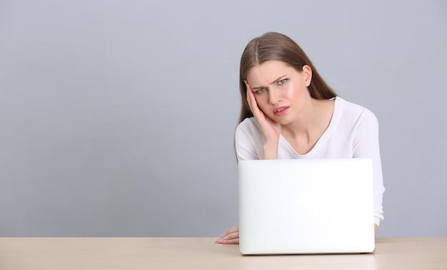 Schöne junge frau, die unter kopfschmerzen leidet, während sie mit laptop, auf grauem hintergrund arbeitet