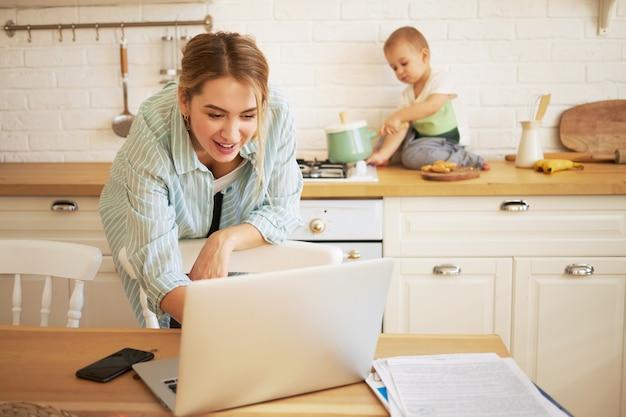 Schöne junge frau, die versucht, mit laptop zu arbeiten und ihren kleinen sohn zu babysitten. nettes baby, das auf küchentheke sitzt und mit topf spielt, seine mutter tippt auf tragbarem computer im vordergrund