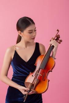 Schöne junge frau, die violine spielt
