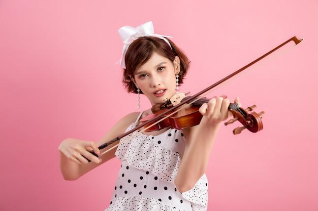 Schöne junge frau, die violine über rosa spielt