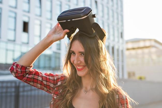 Schöne junge frau, die virtual-reality-headset in einem städtischen kontext trägt