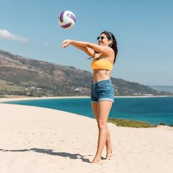 Schöne junge frau, die volleyball am strand spielt