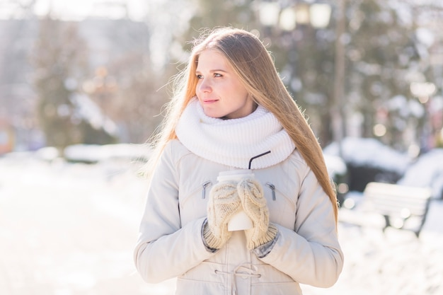 Schöne junge frau, die wegwerfbaren kaffee im winter hält