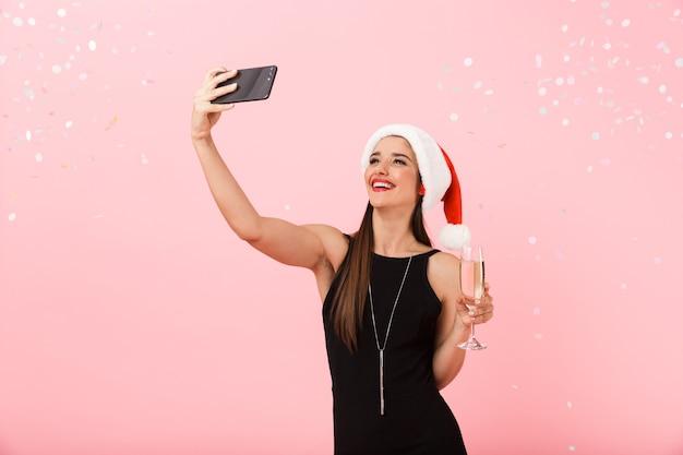 Schöne junge frau, die weihnachtsmütze trägt, die lokal über rosa hintergrund steht und glas glitzernden champagner hält, ein selfie nehmend