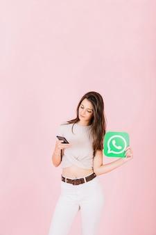 Schöne junge frau, die whatsapp ikone unter verwendung des handys hält
