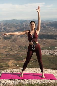 Schöne junge frau, die yoga auf bergen tut
