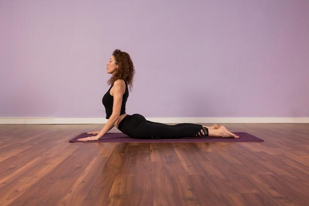 Schöne junge frau, die yoga drinnen praktiziert