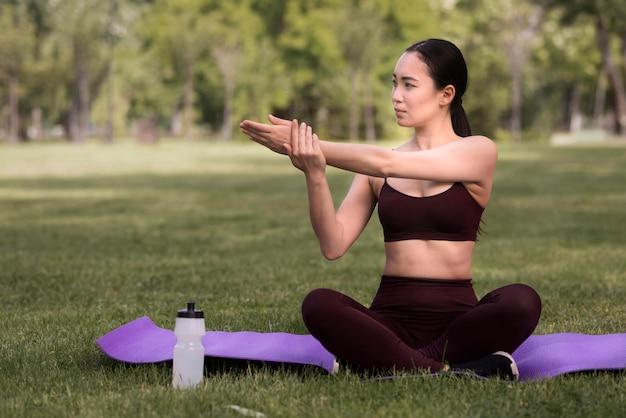 Schöne junge frau, die yoga im freien tut