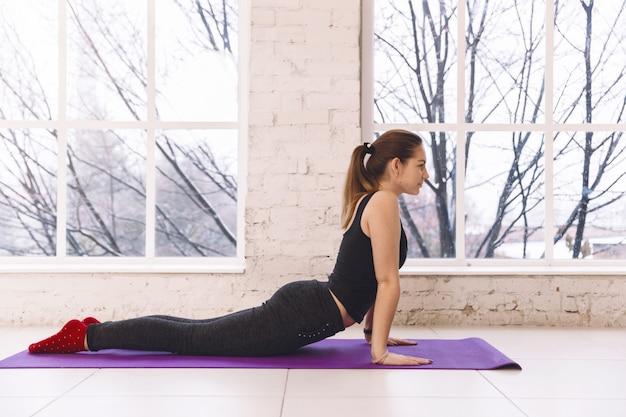 Schöne junge frau, die yoga in der haltung von urdhva-mukha shvanasana im yogastudio auf dem boden nahe dem fenster tut.
