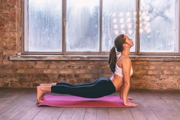Schöne junge frau, die yoga in der haltung von urdhva-mukha shvanasana in der yogahalle auf dem bretterboden nahe dem fenster tut.
