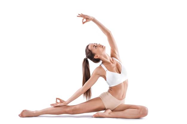 Schöne junge frau, die yoga oder pilatesübung lokalisiert auf weißem hintergrund tut. konzept des gesunden lebens und des gleichgewichts zwischen körperlicher und geistiger entwicklung. volle länge