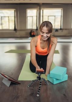 Schöne junge frau, die yoga praktiziert, ist online über ein tablet mit dem lehrer beschäftigt. heimsportkonzept.