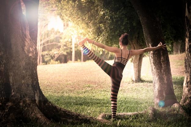 Schöne junge frau, die yogaübung auf grünem gras im park tut
