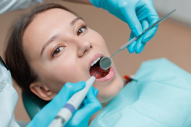 Schöne junge frau, die zahnbehandlung an der zahnarztpraxis hat.