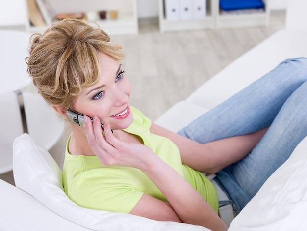 Schöne junge frau, die zu hause am telefon spricht - drinnen