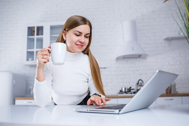 Schöne junge frau, die zu hause auf einem laptop studiert. ein mädchen mit langen blonden haaren in einem pullover trinkt tee in der küche. arbeiten sie aus der ferne von zu hause aus