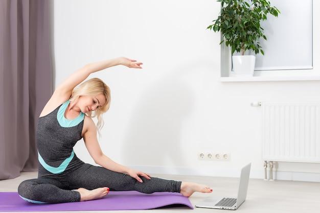 Schöne junge frau, die zu hause dehnübungen auf dem boden macht, online-training auf laptop-computer, kopienraum. porträt in voller länge. yoga, pilates, fitnesstraining