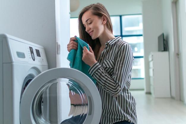Schöne junge frau, die zu hause den geruch des frischen sauberen tuches nach wäscherei riecht und genießt