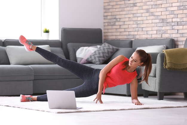 Schöne junge frau, die zu hause fitnessübungen macht