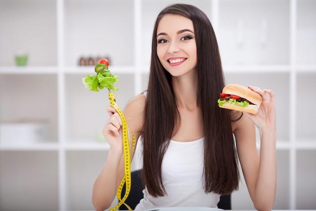 Schöne junge frau, die zwischen gesundem essen und junk food wählt