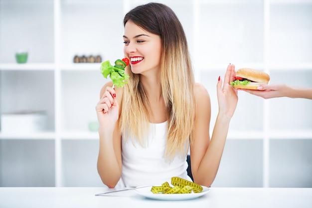 Schöne junge frau, die zwischen gesundem lebensmittel und ungesunder fertigkost wählt