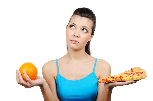 Schöne junge frau, die zwischen pizza und orange wählt