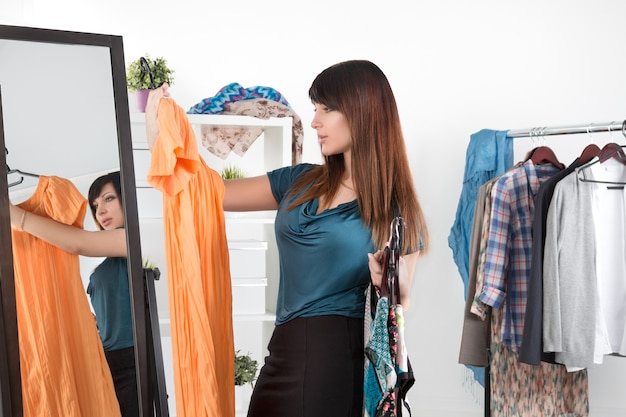 Schöne junge frau, die zwischen spiegel und gestell mit kleidern steht, die chioce machen