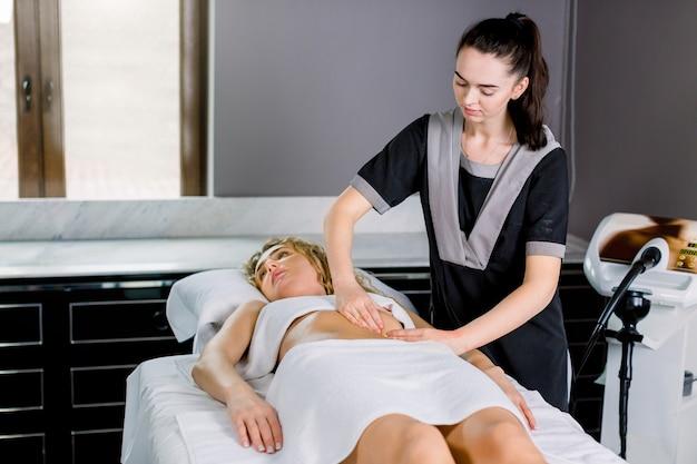 Schöne junge frau doktor massagetherapeutin in einem kosmetikraum, der eine bauchmassage zur jungen blonden frau tut