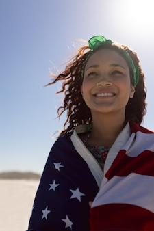Schöne junge frau eingewickelt in der amerikanischen flagge auf strand im sonnenschein