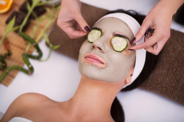 Schöne junge frau erhält gesichtslehmmaske am badekurort