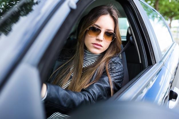 Schöne junge frau fährt ihr auto.