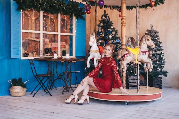 Schöne junge frau freut sich nahe einem karussell mit pferden. weihnachten.