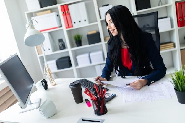 Schöne junge frau füllt die dokumente aus und sitzt im büro am tisch.