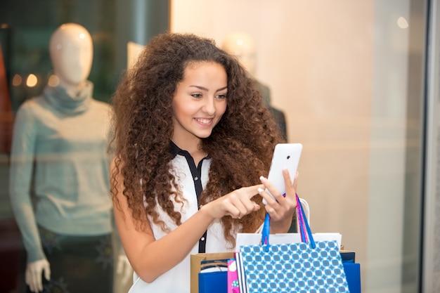 Schöne junge frau geht einkaufen