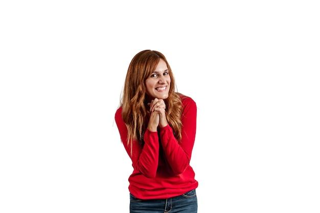 Schöne junge frau gekleidet in einem roten pullover, der glück ausdrückt, lokalisiert auf einem weißen hintergrund