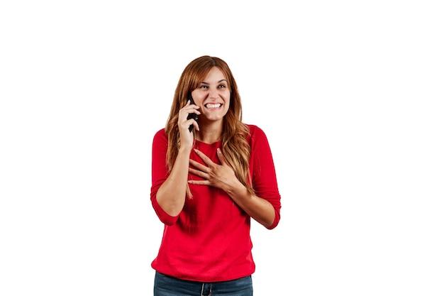 Schöne junge frau gekleidet in einem roten pullover, sehr glücklich, am telefon zu sprechen, lokalisiert auf einem weißen hintergrund