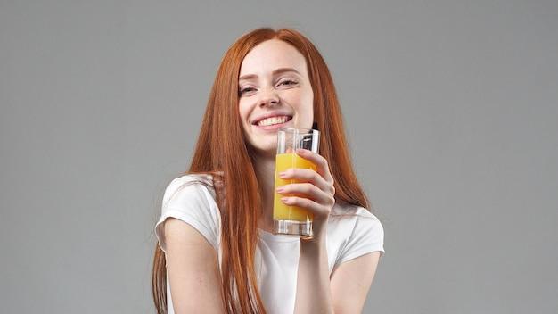 Schöne junge frau glücklich und orangensaft trinkend. junge frau, die glas orangensaft hält