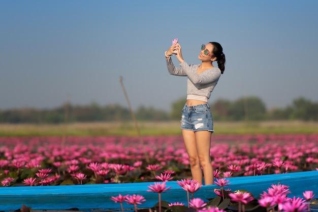Schöne junge frau glücklich, während ein selfie mit dem telefon auf dem boot genommen wird