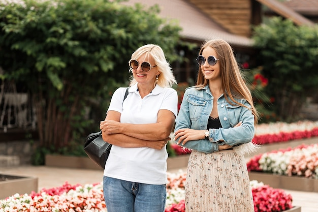 Schöne junge frau glückliche mutter mit lächelnder tochter mit sonnenbrille im weißen polo-t-shirt mit nackten jeans und einer jacke mit rock ruht und wandert auf dem land
