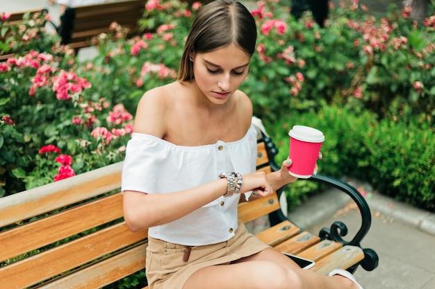 Schöne junge frau hält eine tasse kaffee und schaut auf die armbanduhr, während sie auf einer bank im park sitzt