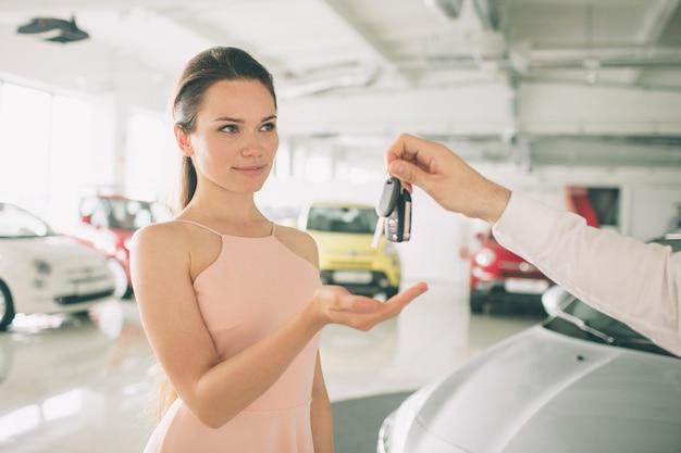 Schöne junge frau hält einen schlüssel im autohaus.
