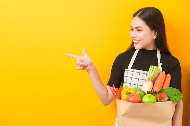 Schöne junge frau hält gemüse in der gelben wand der einkaufstüte