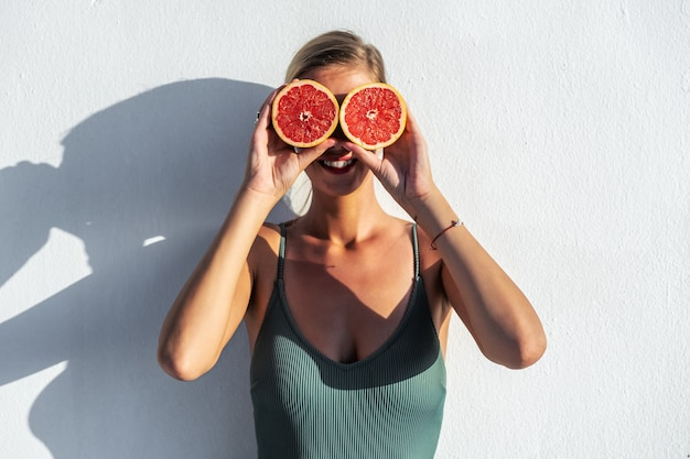 Schöne junge frau hält geschnittene grapefruit in ihren händen nahe augen.