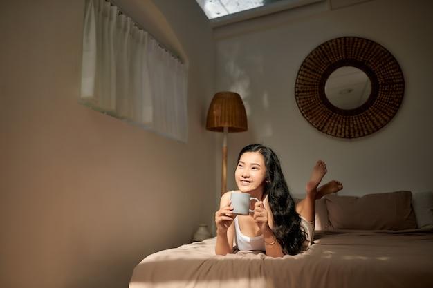 Schöne junge frau hält tasse kaffee liegend denken entspannend auf dem bett, glückliches lächeln tagträumen mit teebecher in den händen