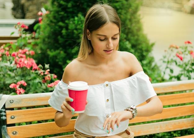 Schöne junge frau hält tasse kaffee und schaut auf armbanduhr