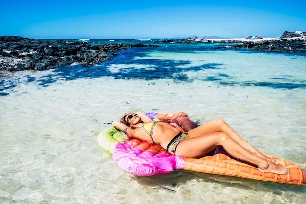 Schöne junge frau hat ein sonnenbad, das sich auf einer trendigen lila aufblasbaren matratze in einer blauen tropischen ozeanlagune mit sand und felsen entspannt - oase und paradieskonzept für reisen und lifestyle and